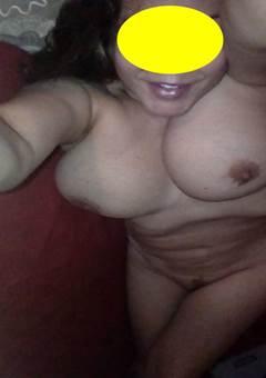 Mulher de meia idade nua exibindo os peitos perfeitos